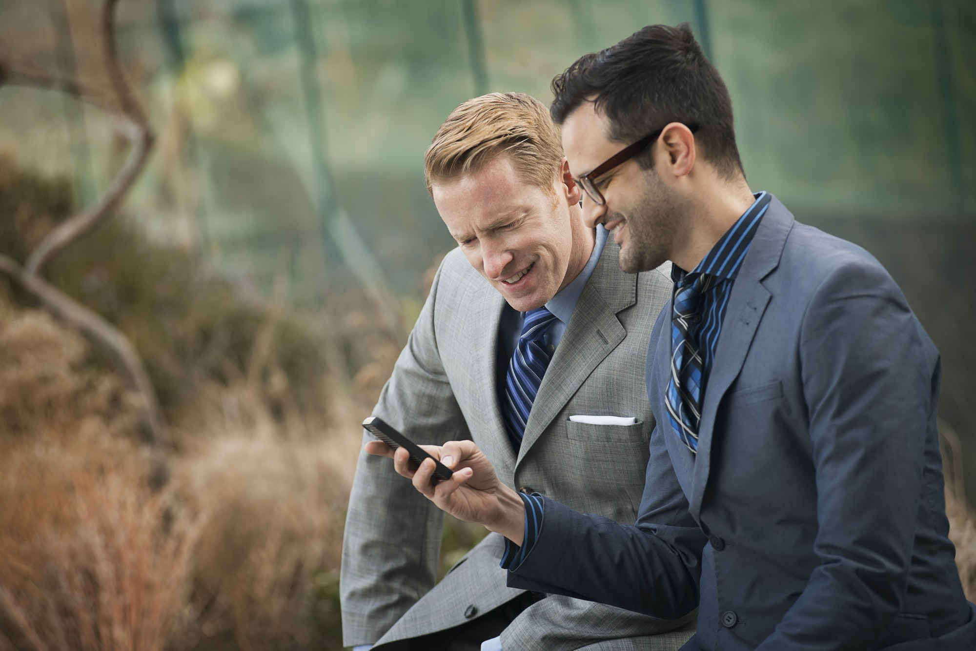Two men standing side by side,looking at a cell phone screen or mobile phone.